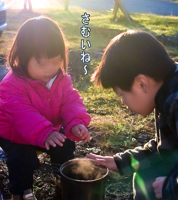 お湯で暖を取る子供二人