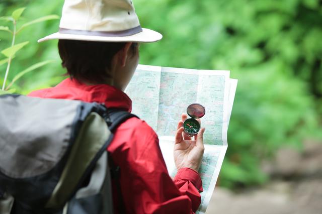 コンパスと地図を見る女性