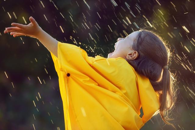 /レインウェアを着て雨に打たれる子供