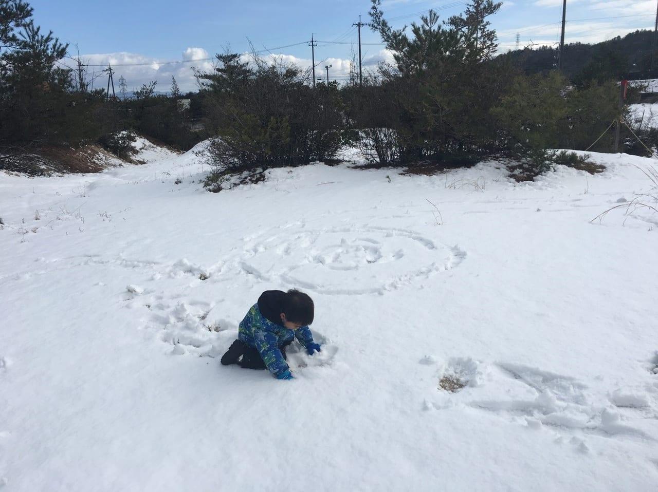 /冬服を着て雪で遊ぶ子供