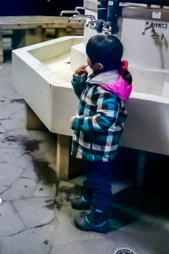/外で歯磨きしている子供-682x1024