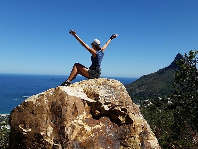 /山頂で手を広げて喜ぶ女性