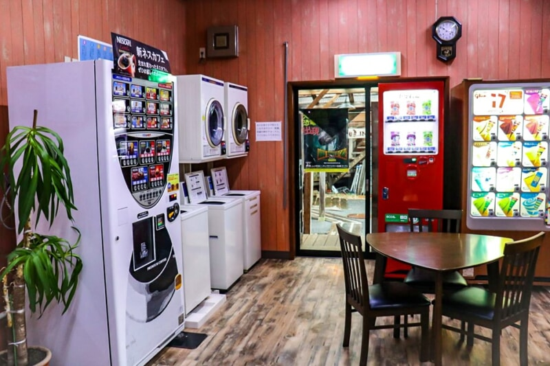 センターハウス内に並ぶ自販機と洗濯機、乾燥機