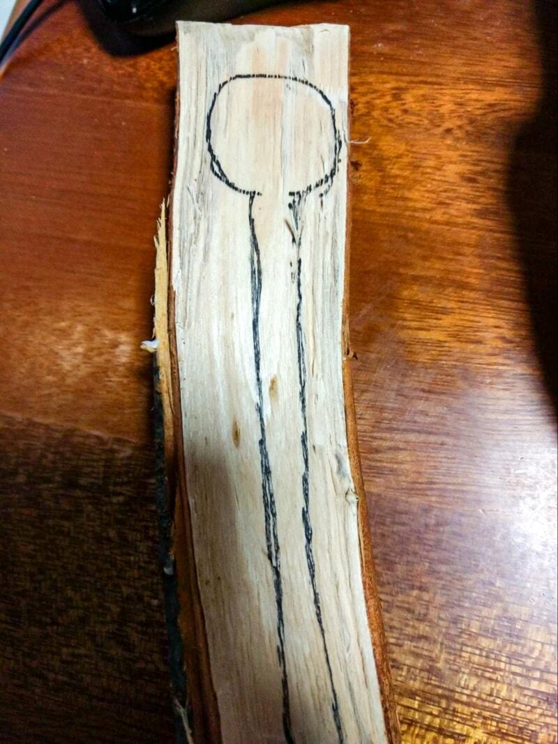 木の断面にマジックでスプーンの設計図を描く