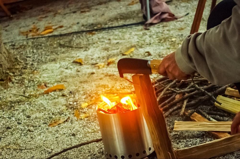 焚き火の前で鉈を使って薪割り