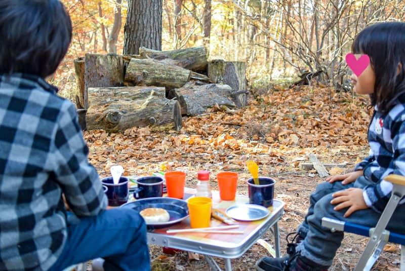 キャンプの朝ごはんをテーブルに並べていただきますを待つ子供