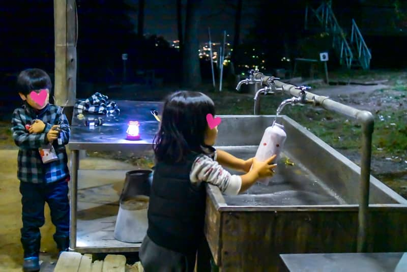水道の水を汲む子供
