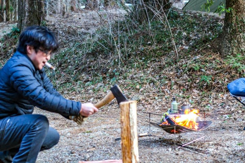 手斧で薪割りをしている男性