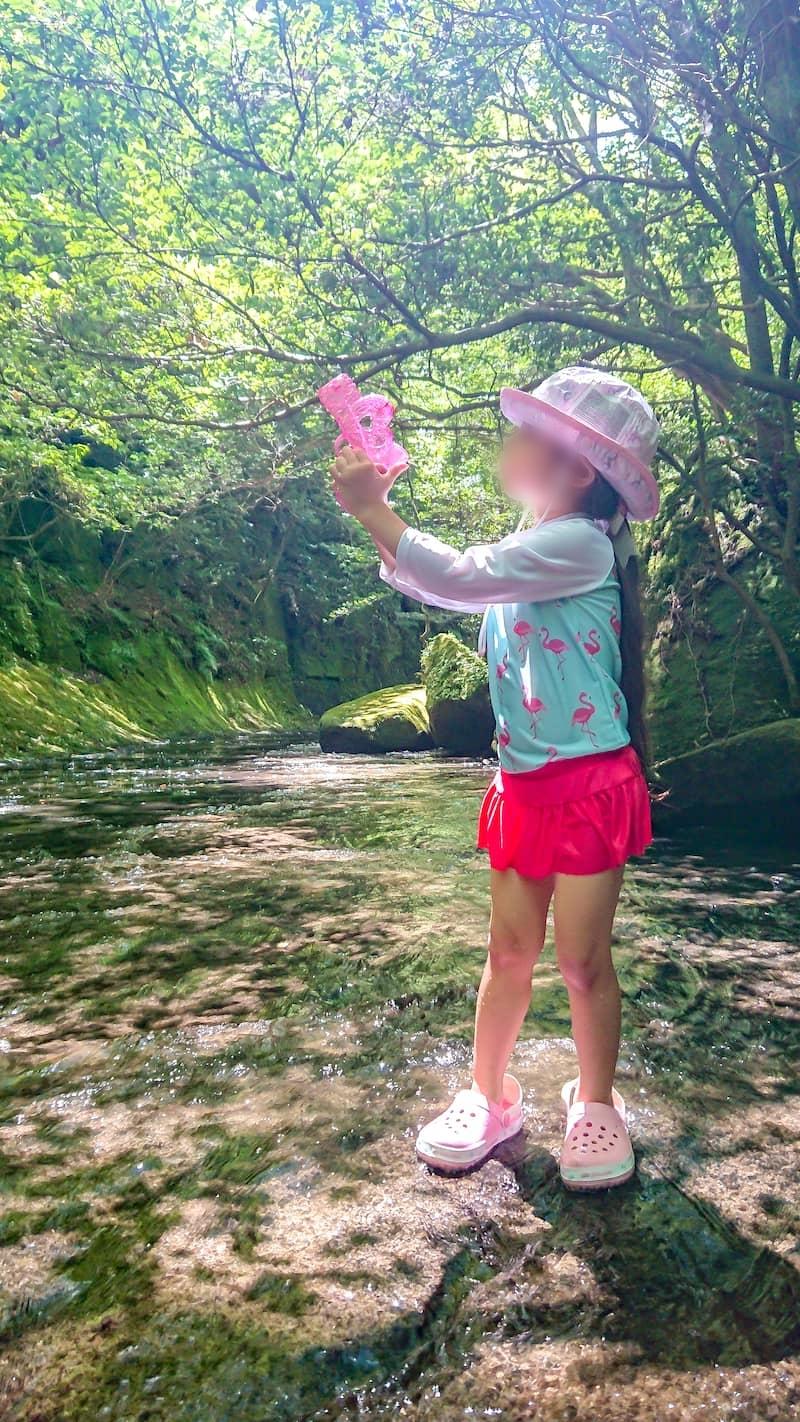 水鉄砲で葉っぱを打って遊ぶ子供