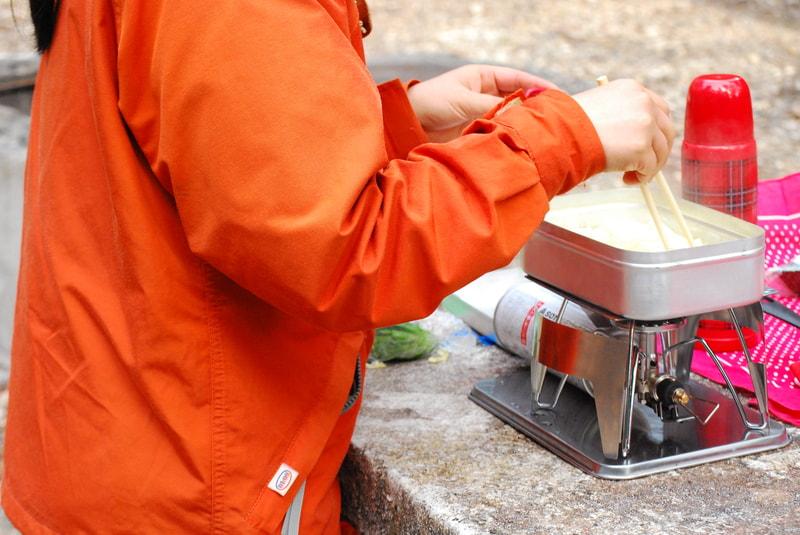 メスティンで食事を作っている女性