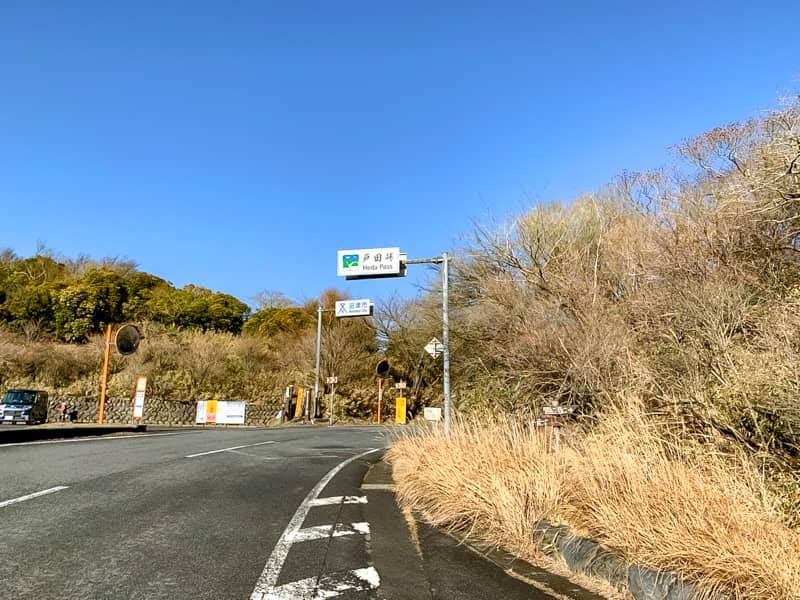 駐車場反対車線の山道に登山口の標識が立っています