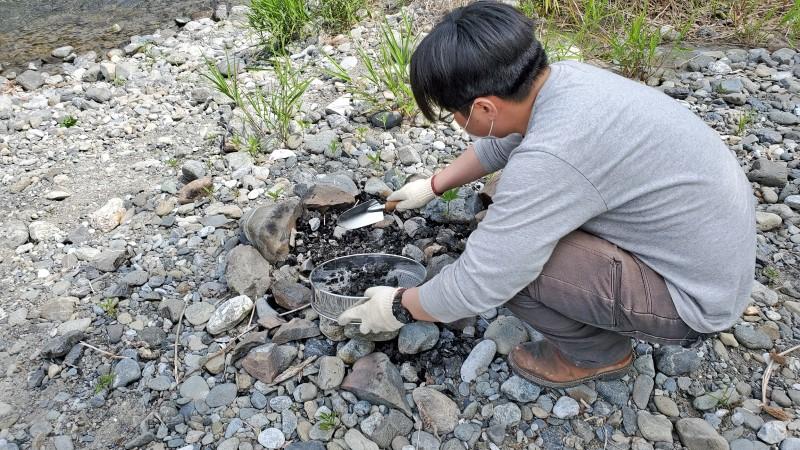 焚火跡を掃除するキャンプクエスト編集部員
