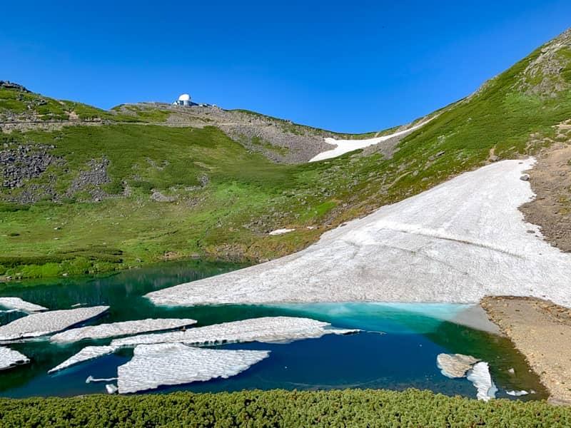右手を見ると、雪が残った湖が目に飛び込んできます